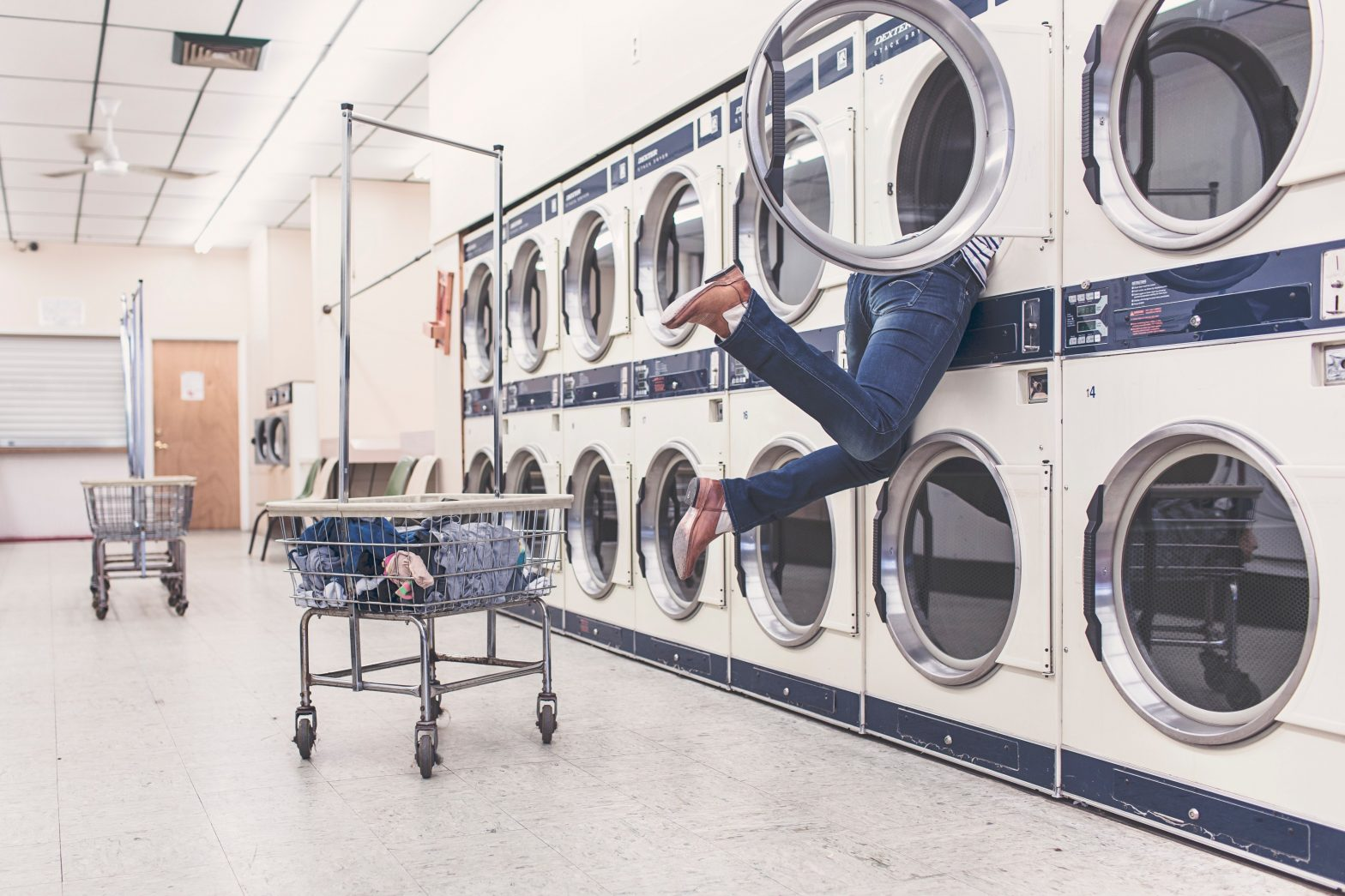 Person head first in washing machine in laundry mat