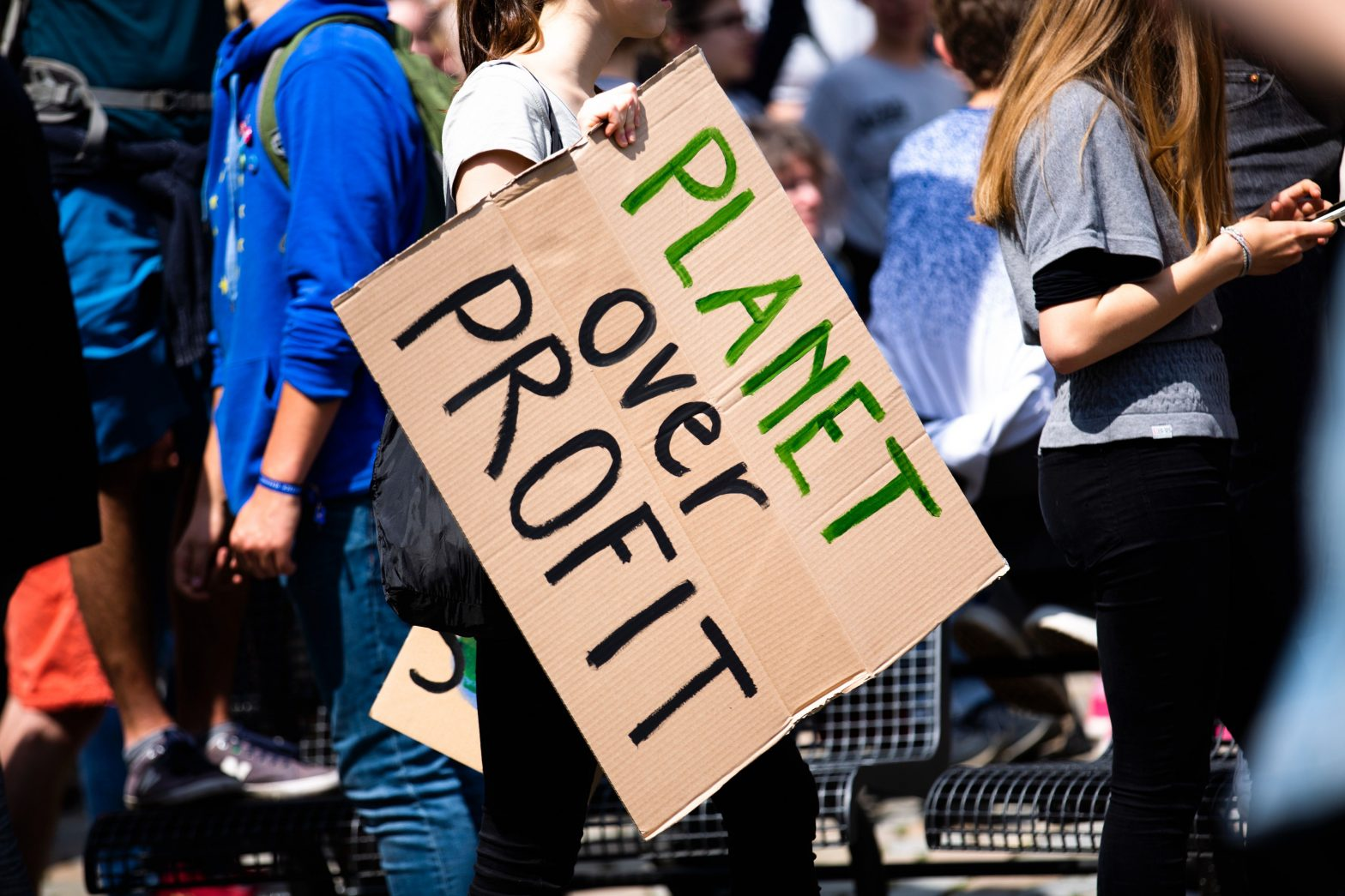 People Protesting with Sign Planet over Profit